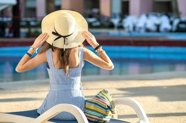 Jonge vrouw lichte zomerjurk en gele stro hoed dragen buiten zitten in de buurt van het zwembad van het hotel op zonnige zomerdag.