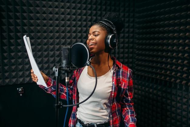 Jonge vrouw liedjes in audio-opnamestudio