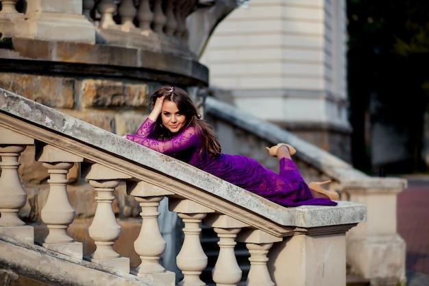 Jonge vrouw liggend op de reling in de buurt van een oud kasteel. schoonheid meisje buitenshuis in het oude kasteel. mooi model meisje in lange jurk. brunette genieten van reizen. gratis gelukkige vrouw