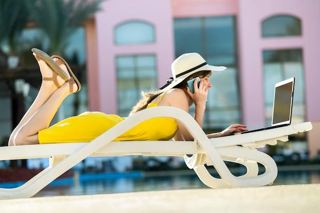 Jonge vrouw liggend op de strandstoel bezig met computer laptop aangesloten op draadloos internet met gesprek op mobiele sellphone in zomerverblijf. zakendoen tijdens het reizen concept.
