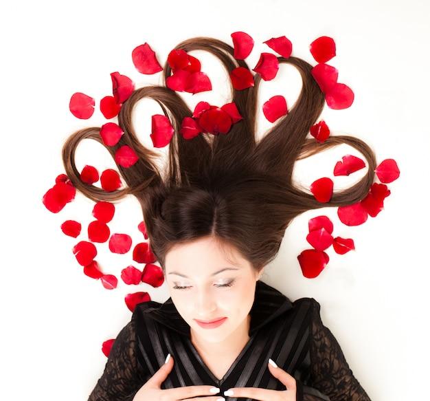 Jonge vrouw liggend op de vloer met rozenblaadjes in haar haar, bovenaanzicht