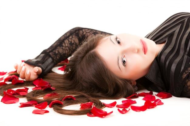 Jonge vrouw liggend op de vloer met rozenblaadjes in het haar