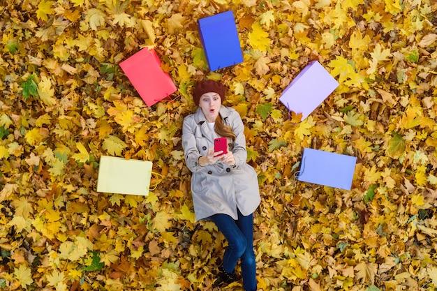 Jonge vrouw liggend op herfstbladeren naast boodschappentassen en selfie te nemen. grote kortingen. bovenaanzicht.