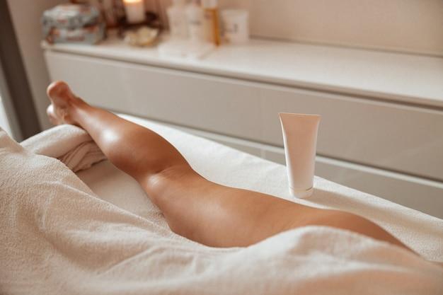 Jonge vrouw liggend op massagetafel in de buurt van cosmetisch product