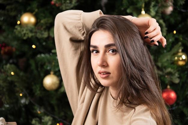 Jonge vrouw liggend op pluizig tapijt in de buurt van kerstboom.