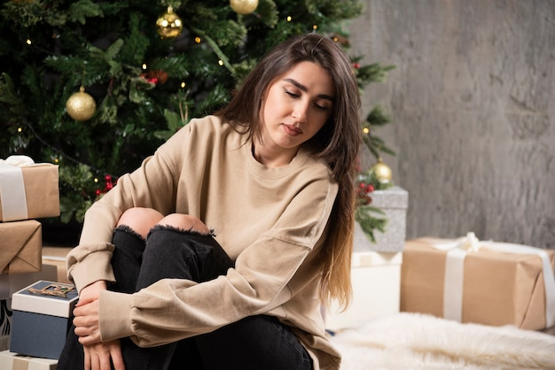 Jonge vrouw liggend op pluizig tapijt met kerstcadeautjes.