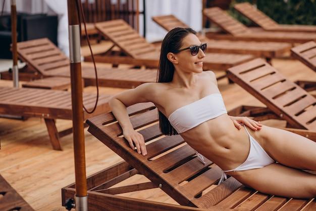 Jonge vrouw liggend op zonnebank bij het zwembad