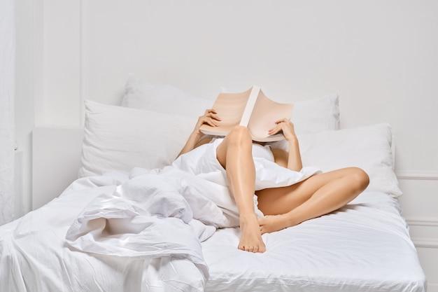 Jonge vrouw ligt in bed en leest een boek. luie ochtend.