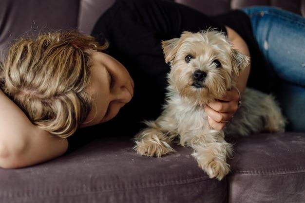Jonge vrouw ligt op roze bank en knuffelt yorkshire terrier hond ze zijn gelukkig en ontspannen samen hond kijkt naar de camera concept van thuiscomfort rust en ontspanning