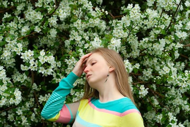 Jonge vrouw lijdt aan allergieën tegen de achtergrond van een bloeiende appelboom