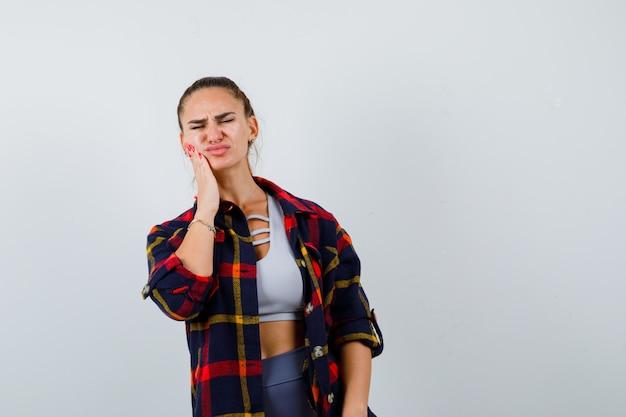Jonge vrouw lijdt aan kiespijn in crop top, geruit hemd, broek en ziet er onwel uit, vooraanzicht.