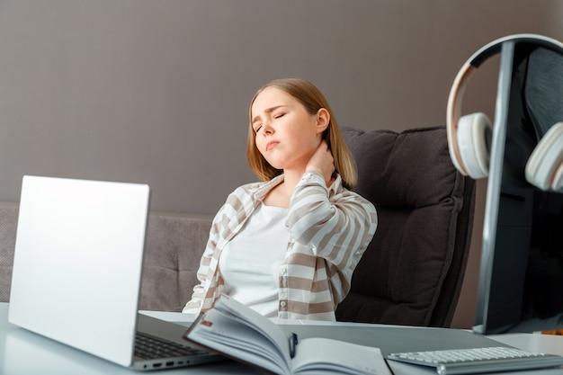 Jonge vrouw lijdt aan nekpijn. vermoeide vrouw heeft hoofdpijn en cervicale rugpijn terwijl ze op kantoor of thuis werkt. tienermeisje heeft pijn in de wervelkolom tijdens online onderwijs.