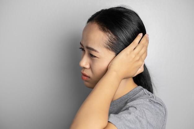 Jonge vrouw lijdt aan oorpijn.