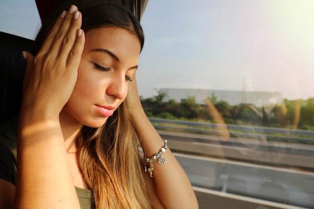 Jonge vrouw lijdt aan ziekte tijdens het reizen met de bus. reisziekte toeristische vrouw op bus met hoofdpijn of misselijkheid.