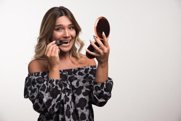 Jonge vrouw lippenstift op witte muur met gelukkige uitdrukking toe te passen.