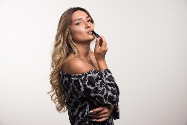 Jonge vrouw lippenstift op witte muur toe te passen tijdens het kijken naar voorzijde.