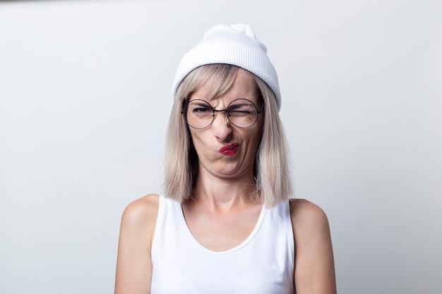 Jonge vrouw loensen grimas bril, een witte dop op een lichte achtergrond.