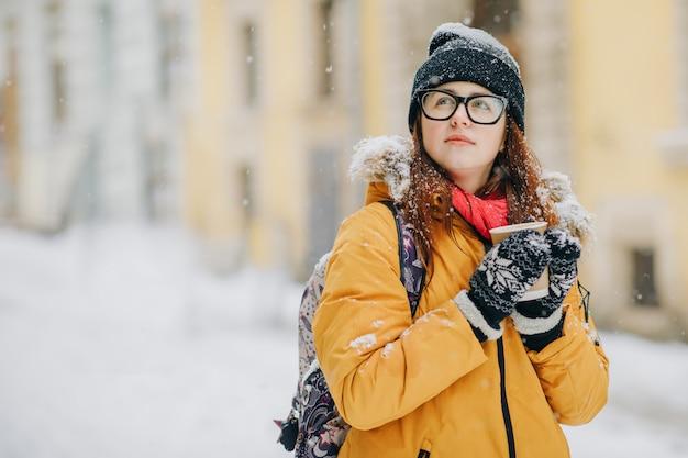 Jonge vrouw loopt door de stad. sneeuw. concept lifestyle, stedelijk, winter
