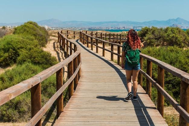 Jonge vrouw loopt door een loopbrug op het strand