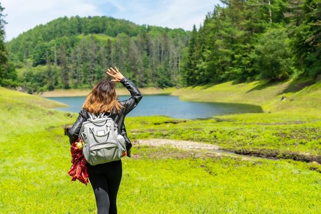 Jonge vrouw loopt door het veld met een meer en een dennenbos