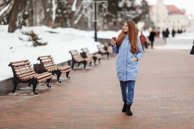 Jonge vrouw loopt in een winterpark met koffie.