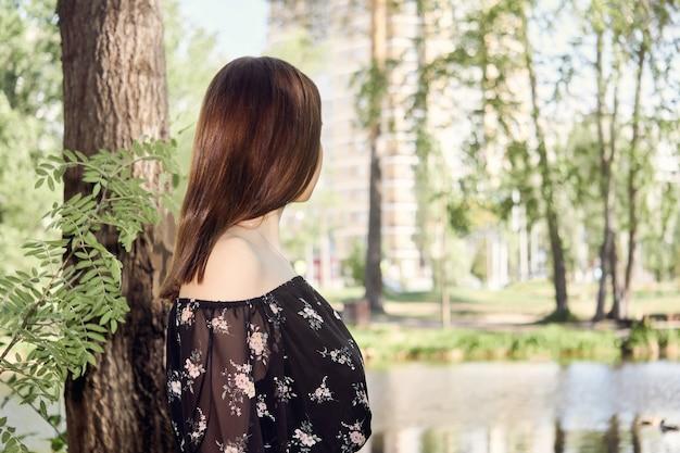 Jonge vrouw loopt in het park en kijkt naar stadsgebouwen in de verte