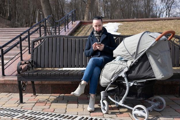 Jonge vrouw loopt in het park in het voorjaar met een kinderwagen