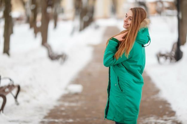 Jonge vrouw loopt in het winterpark. winterpark in de sneeuw. kleding reclame foto concept.