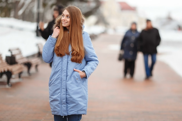 Jonge vrouw loopt in het winterpark. winterpark in de sneeuw.