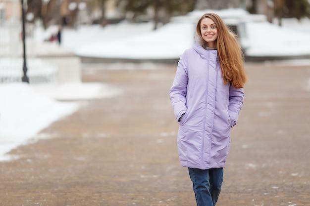 Jonge vrouw loopt in het winterpark.