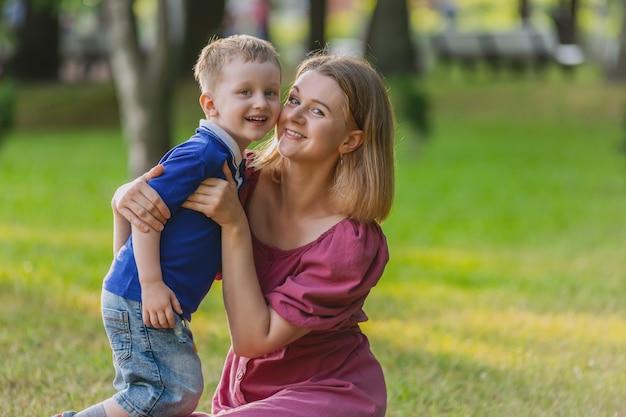 Jonge vrouw loopt in park met driejarig jongetje