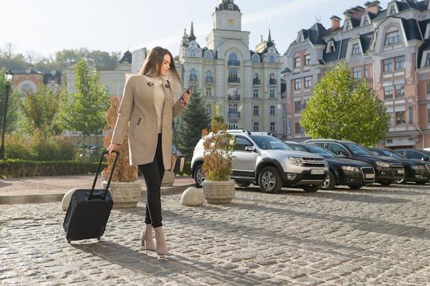 Jonge vrouw loopt langs stadsstraat met reiskoffer