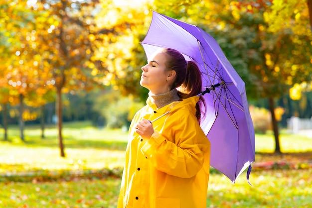 Jonge vrouw loopt op een zonnige dag gouden herfst in het park meisje met paraplu en regenjas genieten van...