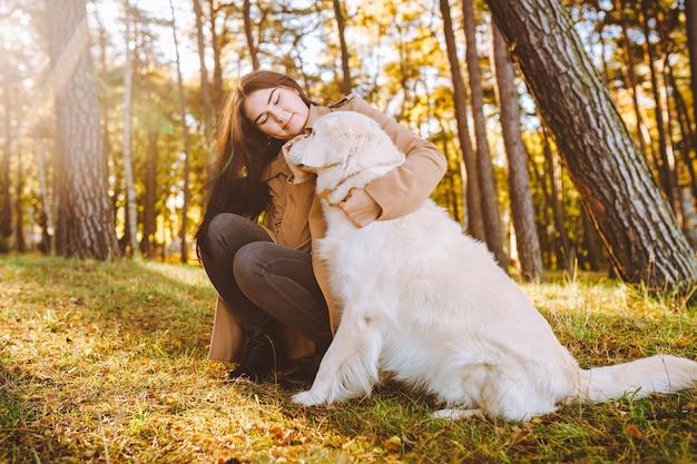 Jonge vrouw lopen en spelen met haar golden retriever in gele herfst park. vriendschap, zorg, huisdier liefde concept.