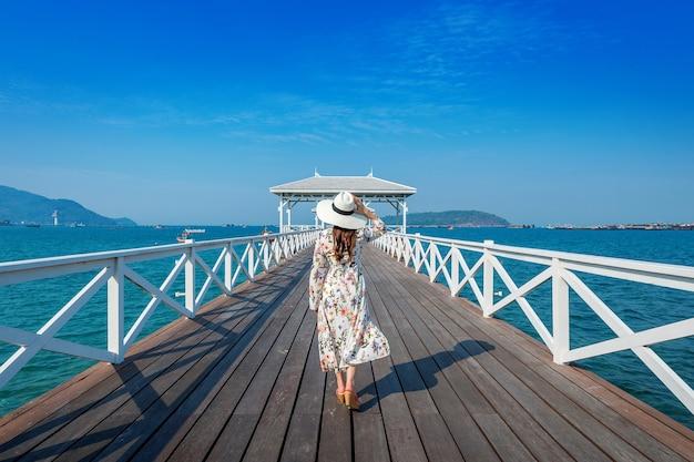 Jonge vrouw lopen op houten brug in si chang island, thailand.