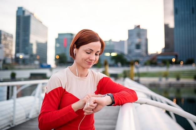 Jonge vrouw loper met koptelefoon in de stad, met behulp van smartwatch tijdens het rusten.