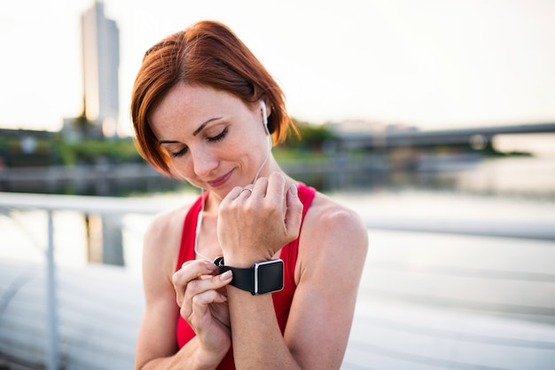 Jonge vrouw loper met koptelefoon in de stad, met behulp van smartwatch tijdens het rusten. Premium Foto