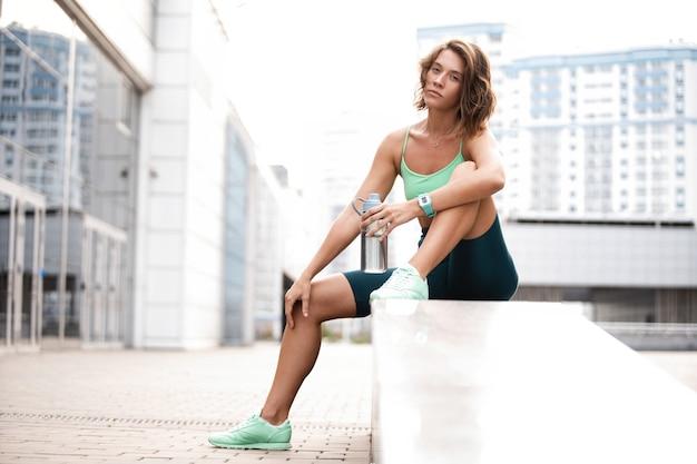 Jonge vrouw loper rusten na training sessie op stedelijke straat