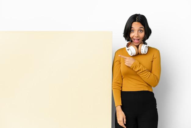 Jonge vrouw luisteren muziek met een groot leeg aanplakbiljet over geïsoleerde achtergrond verrast en wijzende kant