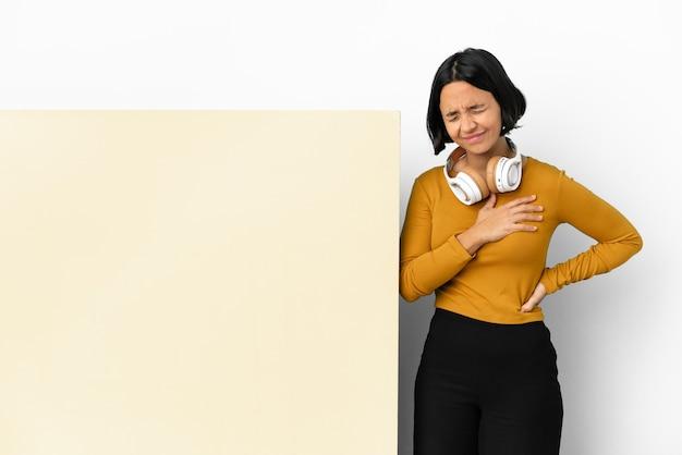 Jonge vrouw luisteren muziek met een groot leeg aanplakbiljet over geïsoleerde muur met pijn in het hart