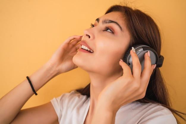 Jonge vrouw luisteren muziek met koptelefoon.