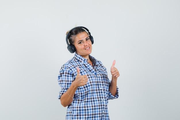 Jonge vrouw luisteren muziek terwijl duim opdagen in geruit overhemd en blij kijken. vooraanzicht.