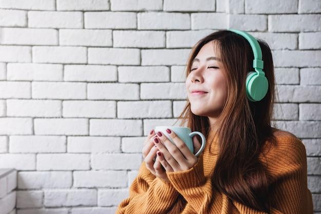 Jonge vrouw luisteren muziek van hoofdtelefoon in gezellige huis