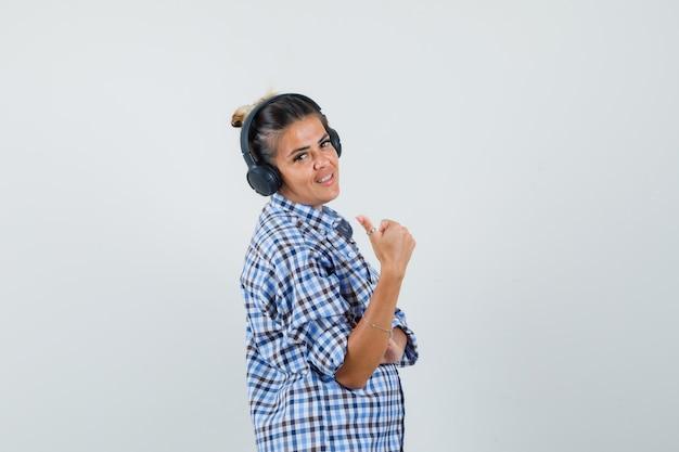 Jonge vrouw luisteren muziek via oortelefoons terwijl duim opdagen in geruit overhemd en blij kijken. .