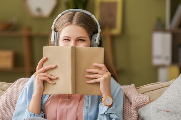 Jonge vrouw luisteren naar audioboek thuis
