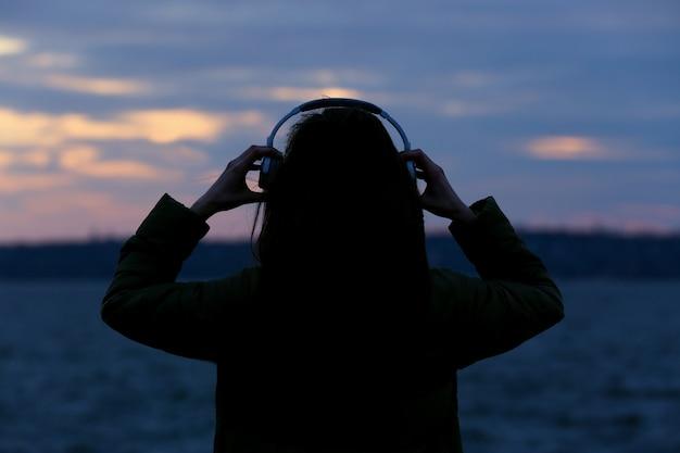 Jonge vrouw luisteren naar muziek in de buurt van de rivier bij zonsondergang