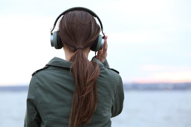 Jonge vrouw luisteren naar muziek in de buurt van rivier