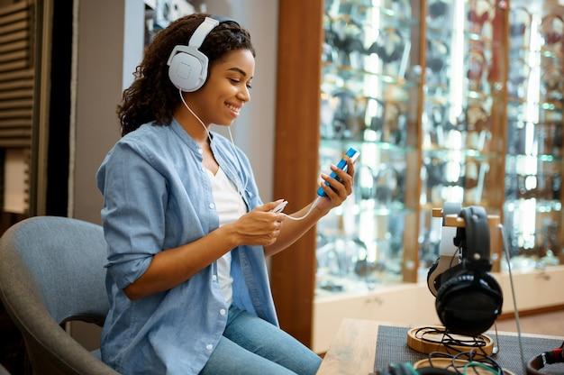 Jonge vrouw luisteren naar muziek in hoofdtelefoons winkel. vrouwelijke persoon in audioshop, showcase met oortelefoons, koper in de multimediawinkel