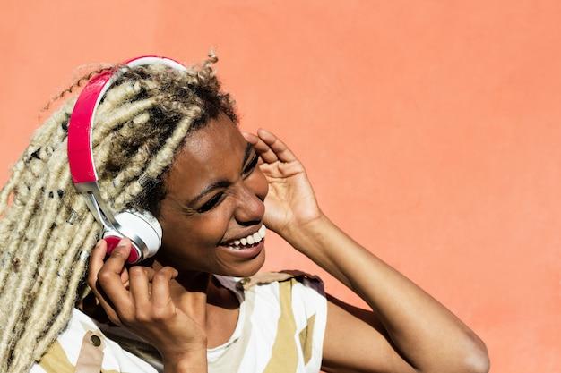 Jonge vrouw luisteren naar muziek met een koptelefoon