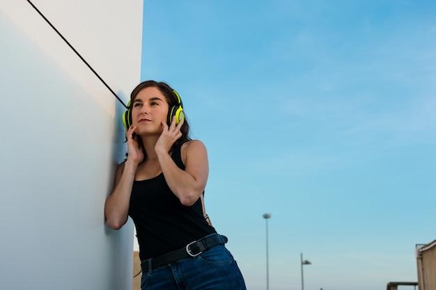 Jonge vrouw luistert muziek via haar koptelefoon